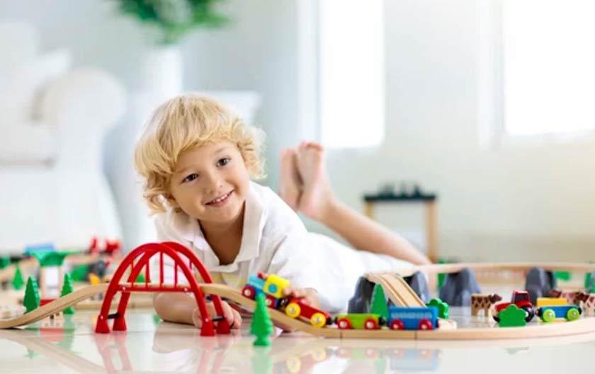 Bambino che gioca con pista e trenino in legno